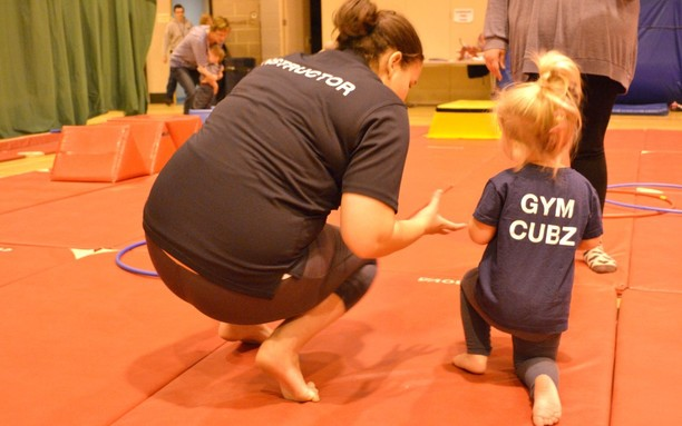 small child gymnast with instructor