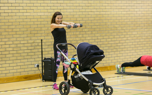 Mum holding weights beside child's buggy