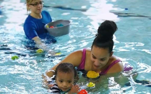 Mother and child in pool with instructor