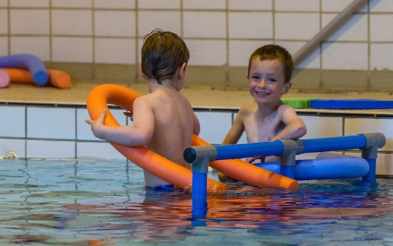 Small boys in pool with noodles