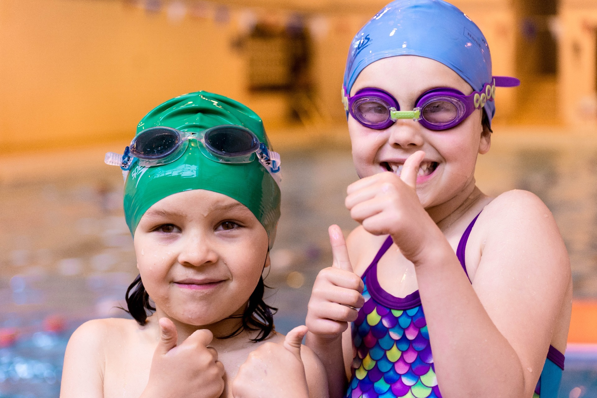 Children in swimming costumes giving thumbs up