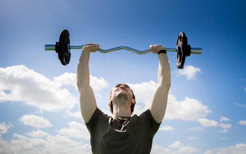 Man holding barbell up into the sky