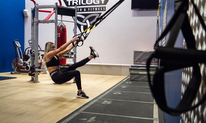 Female in gym TRX training