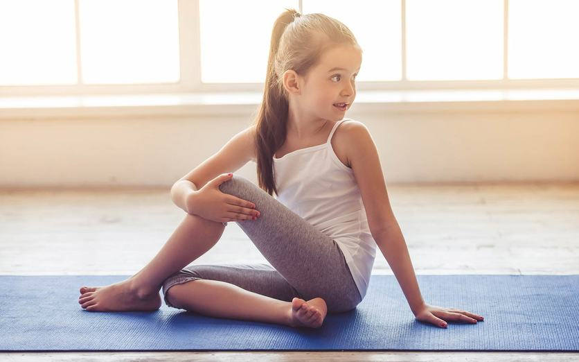 Young girl stretching on gym mat